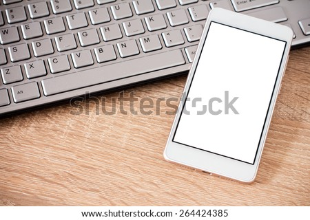 Smartphone laying on laptop keyboard with copy space on screen - stock photo