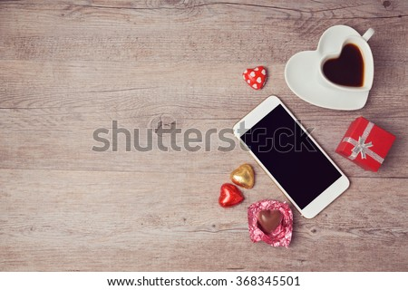 Smartphone mock up flat lay for Valentine's day with coffee cup and chocolate. View from above - stock photo