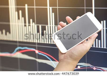 Smartphone on hand with stock market chart graphs background - stock photo