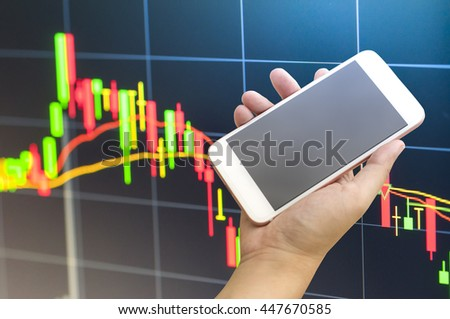 Smartphone on hand with stock market graph background - stock photo