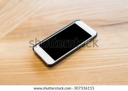 Smartphone on wood table. - stock photo