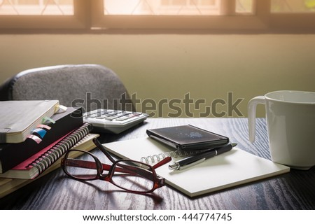 Smartphone put down on table beside notebooks and pen in morning time on work day. Business working at home concept - stock photo