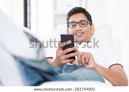 Smartphone social media concept. Indian guy using mobile phone. Asian man relaxed and lying on sofa indoor. Handsome male model.