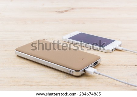 Smartphone with golden powerbank on wood desk. - stock photo