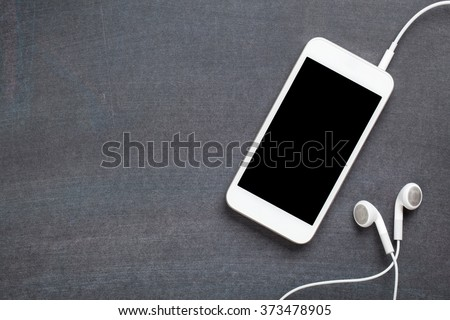 Smartphone with headphones on blackboard background. Top view with copy space - stock photo