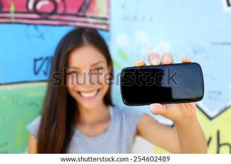 Smartphone - young ethnic woman showing screen for copyspace for text or photo. Asian young adult holding phone with urban graffiti background at Berlin wall, Germany.