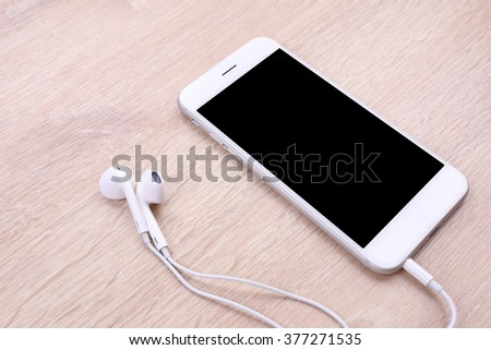 smartphones mockup with earphone on wooden background - stock photo
