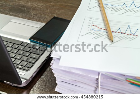Smartphones on laptop near documents stack and pencil - stock photo