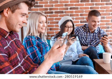 Smartphones rule the world. Young handsome boy and his friends sitting in a cafe. All using their mobile phones instead of talking to each other selective focus - stock photo