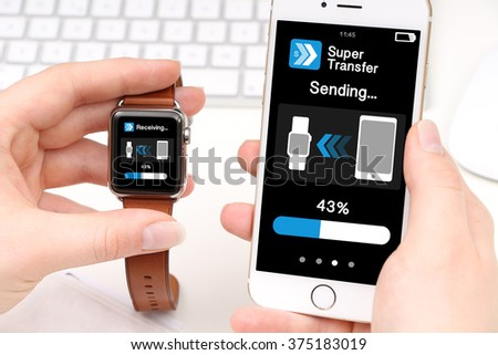 Smartwatch and smartphone transferring data - stock photo