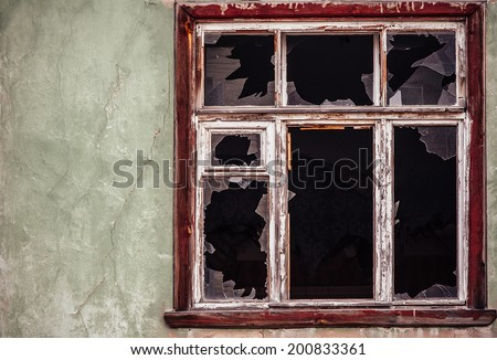 Smashed glass Window with old wooden frame on grunge wall damaged house - stock photo