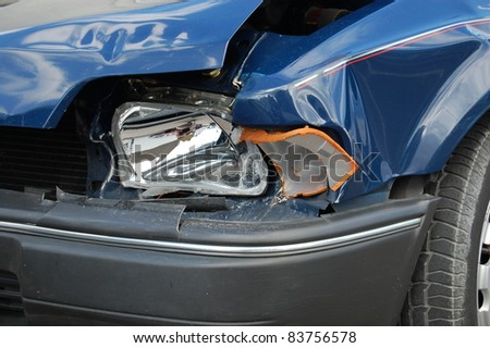 Smashed Headlight. Close-up of a smashed headlight on a blue car. - stock photo
