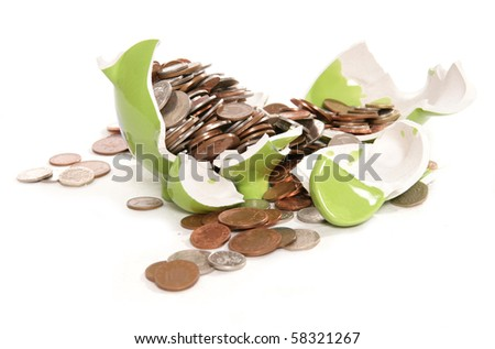 smashed piggy bank moneybox with British currency coins - stock photo