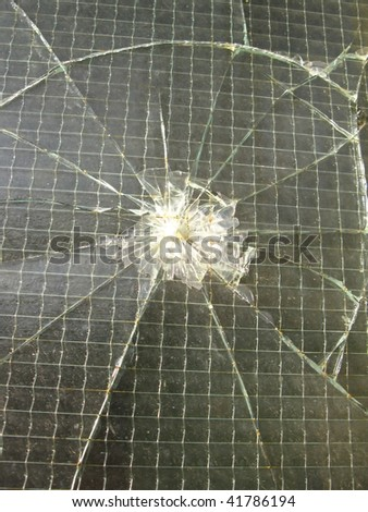 smashed reinforced glass in the window of an old factory hall metal plant