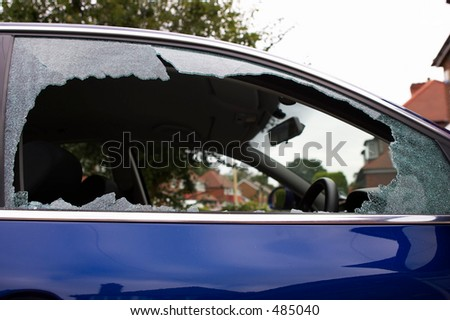 Smashed safety glass in a car door - stock photo