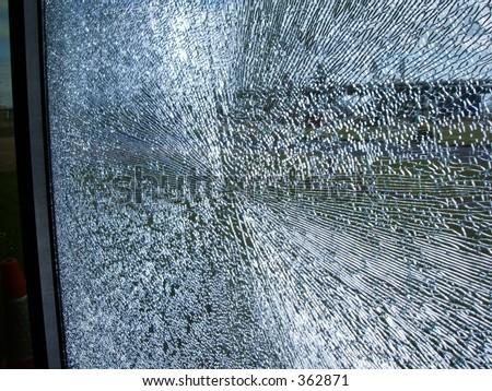 smashed shattered glass window pane gunshot cracks shards splinters pattern - stock photo