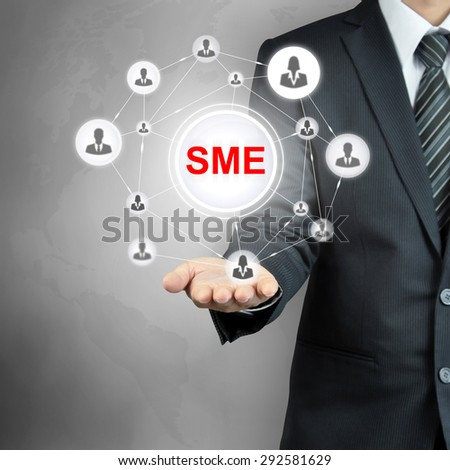 SME (or Small and Medium Enterprises) sign with people icon network on businessman hand - stock photo