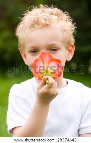 Smelling a flower by a boy. - stock photo