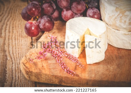 Smelly blue cheese on a wooden rustic table with grape