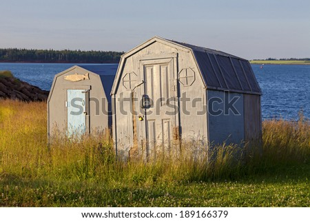 Smelt shacks or buildings used in ice fishing, hauled up on the shore waiting for winter for the ice to return, in rural Prince Edward Island, Canada.