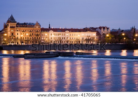 Smetana embankment in Prague with city houses at night illumination. Winter view.