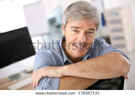 Smiiling mature man relaxing in office chair - stock photo