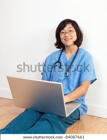 Smiing female nurse or doctor, seated on floor with laptop computer - stock photo