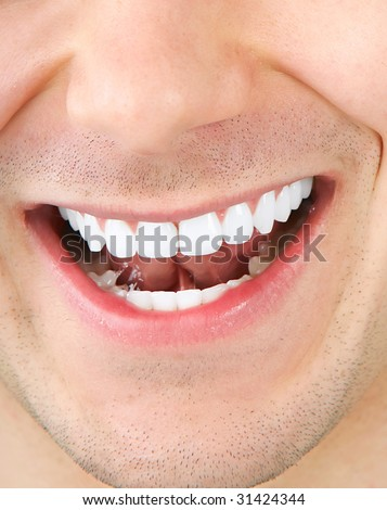 Smile and teeth of a young smiling  man. Close up - stock photo