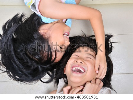 smile asian children lying in bed and playing, top view