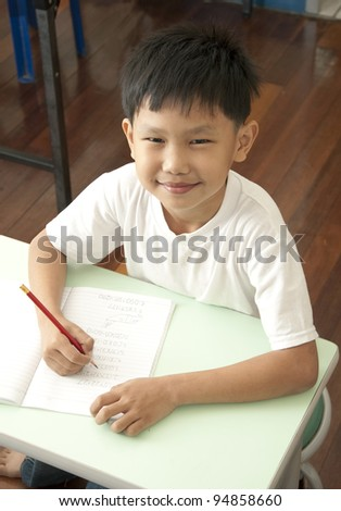 Smile Asian kid writes on notebook in classroom - stock photo