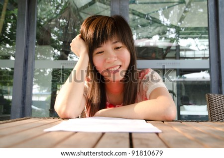 smile asian woman on desk with paper outdoor - stock photo