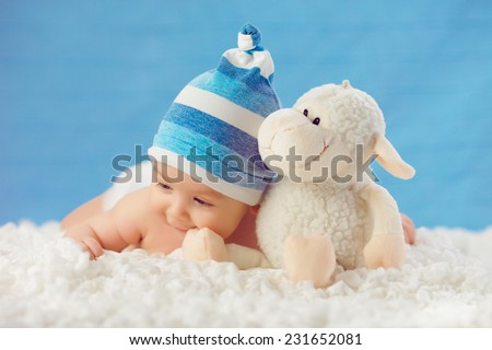 Smile baby in hat, hugging toy on a white bedspread, on a blue background - stock photo