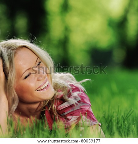 smile blonde lying on green grass - stock photo