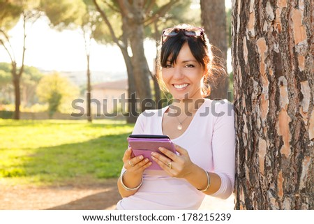 Smile brunette woman reading her e-book outdoor - stock photo