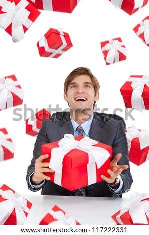 smile business man hold red gift box sitting at the desk, present fall fly around, isolated over white background, concept of holiday celebrate new year christmas birthday anniversary - stock photo