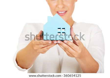 Smile businesswoman holding a paper house - stock photo
