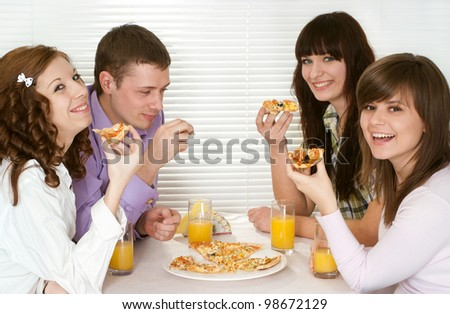 Smile Caucasian group of four people with pizza and juice sitting in a cafe