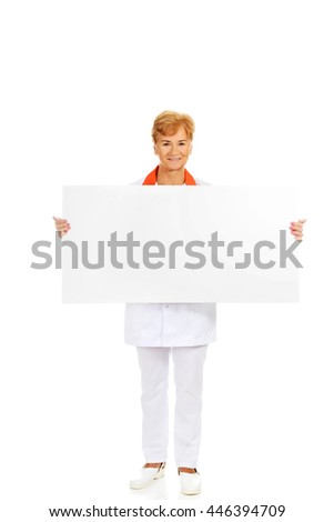 Smile elderly female  doctor or nurse holding blank banner