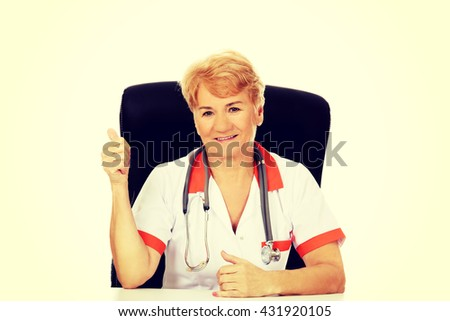 Smile elderly female doctor or nurse sitting behind the desk and shows thumb up - stock photo