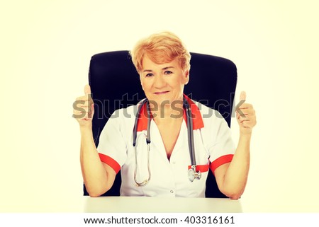 Smile elderly female doctor or nurse sitting behind the desk and shows thumbs up - stock photo