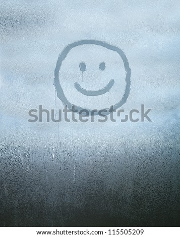 Smile face drawn over condensed glass - stock photo