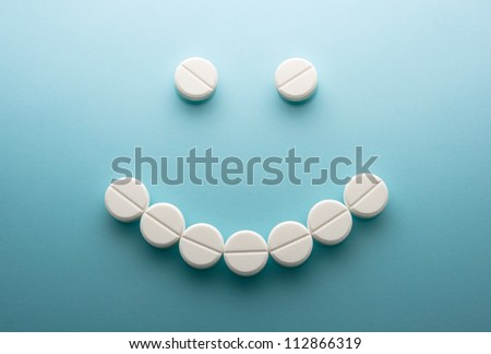 Smile face  from pills  on blue background - stock photo