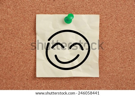 Smile face sticky note pinned on cork board. - stock photo