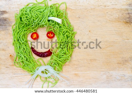 smile faces on wood background made from vegetable and noodle with space for your text. - stock photo