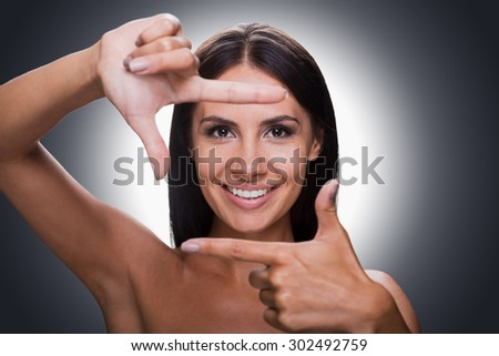 Smile for the camera! Portrait of happy young shirtless woman looking at camera and gesturing finger frame while standing against grey background - stock photo