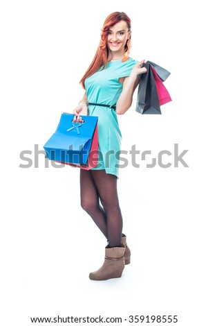 Smile girl standing with shopping bags, isolated on white background. Full length - total figure