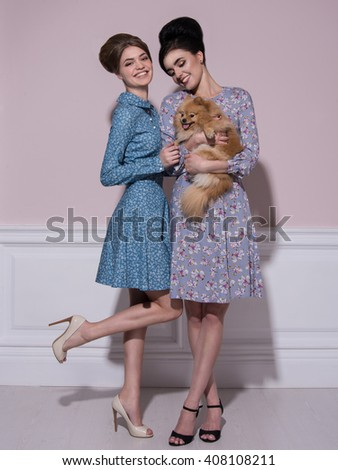 smile girlfriend, girlfriends, girls in ' 60s style, blonde and brunette, beautiful girls dresses in flowers, cheerful girls, sunshine, girls walking laughing,girl with a dog,girls with Spitz - stock photo