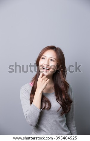 Smile happy woman look something isolated on gray background, asian beauty