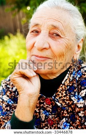 Smile of elegant content senior woman outdoor - stock photo