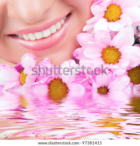 Smile of young woman with flowers - stock photo